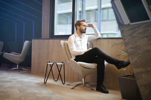 muž sedí na židli